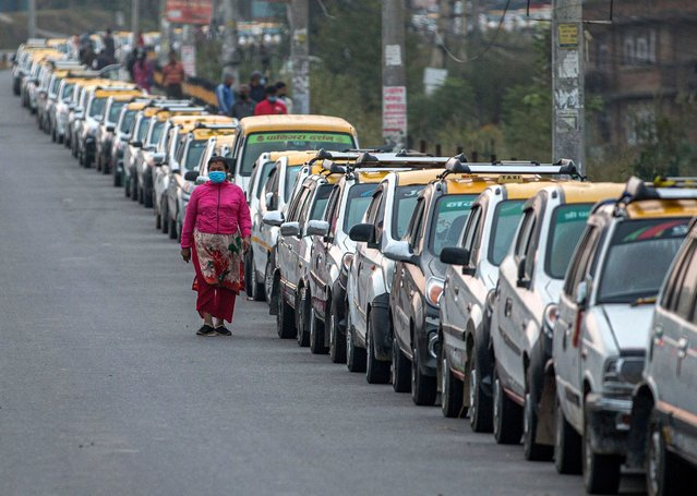 A woman walks past a line of parked taxis in Lalitpur, Nepal, 14 October 2020. (Photo by Narendra Shrestha/EPA/EFE)