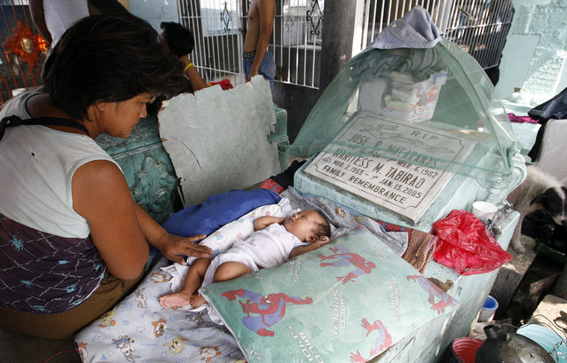 A baby rests on a tomb inside a slum in a public cemetery of Manila, October 27, 2010. (Photo by Cheryl Ravelo/Reuters)