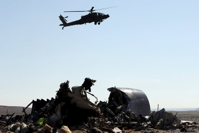An Egyptian military helicopter flies over debris from a Russian airliner which crashed at the Hassana area in Arish city, north Egypt, November 1, 2015. (Photo by Mohamed Abd El Ghany/Reuters)