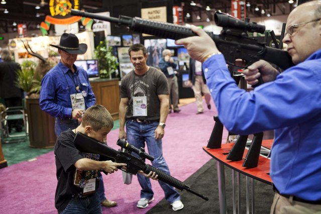 Eleven-year-old Harrison Atwood (L) and Tony Miele (R) test Trijicon rifle scopes at the Safari Club International Convention in Reno, Nevada January 29, 2011. U.S. President Barack Obama is expected to address gun control soon, in the wake of the Tucson shootings, local media reported. (Photo by Max Whittaker/Reuters)