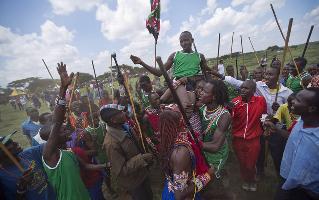 Maasai run, whoop and hold up a young warrior from their village after he won a running competition, at the annual Maasai Olympics in the Sidai Oleng Wildlife Sanctuary near to Mt Kilimanjaro, in southern Kenya Saturday, December 13, 2014. (Photo by Ben Curtis/AP Photo)