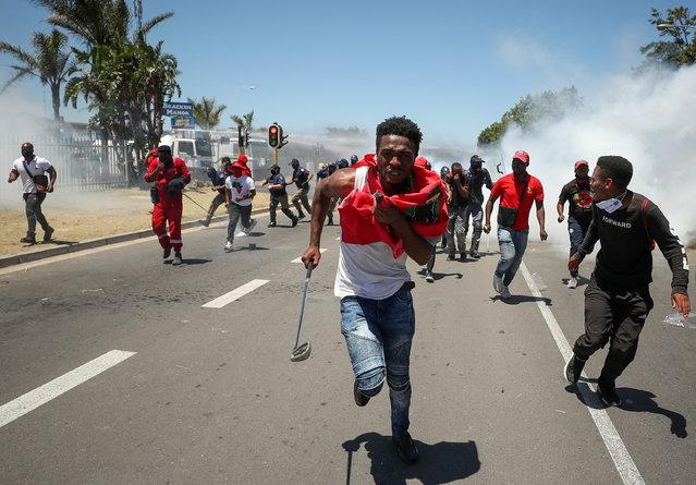 People run away from teargas during the opposition Economic Freedom Fighters party's protest against alleged racism outside Brackenfell High School in Cape Town, South Africa, November 20, 2020. (Photo by Mike Hutchings/Reuters)