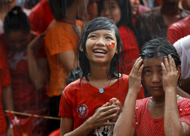 Supporters celebrate as they wait for official results from the Union Election Commission during heavy rain fall in front of the National League for Democracy Party (NLD) head office at Yangon, November 9, 2015. Myanmar's ruling party conceded defeat in the country's general election on Monday, as the opposition led by democracy figurehead Aung San Suu Kyi appeared on course for a landslide victory that would ensure it can form the next government. (Photo by Soe Zeya Tun/Reuters)
