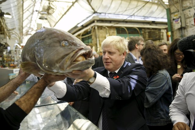 London's mayor Boris Johnson holds a fish while touring the Mahane Yehuda market in Jerusalem November 10, 2015. (Photo by Ronen Zvulun/Reuters)