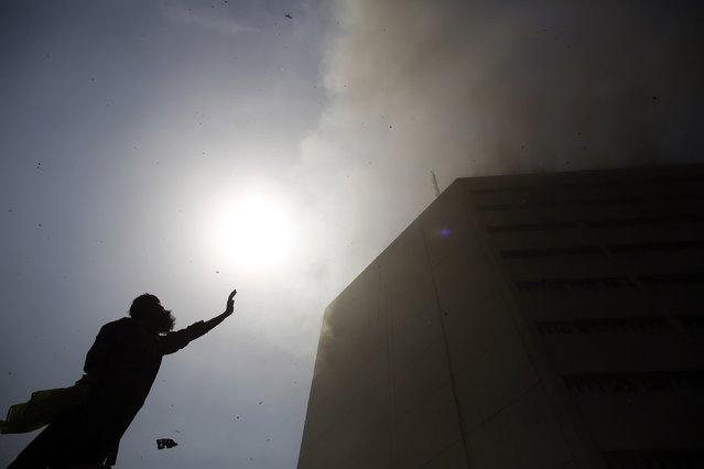 A man gestures toward a rescue helicopter as it approaches a burning building in central Lahore May 9, 2013. Fire erupted on the seventh floor of the LDA plaza in Lahore and quickly spread to higher floors leaving many people trapped inside the building. At least three people fell from the high floors trying to avoid the fire that engulfed the building, local media reports. (Photo by Damir Sagolj/Reuters)