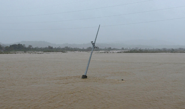 A utility pole is partially submerged in a river after Typhoon Haima struck San Nicolas, Ilocos Norte in northern Philippines, October 20, 2016. (Photo by Ezra Acayan/Reuters)