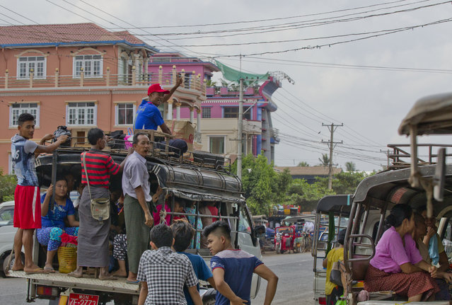 In this April 9, 2017 photo, Myint Naing sitting on a roof of a public transport vehicle, waves at Mudon, Mon State, Myanmar. Myint desperately wants to work, but he's simply not able. Muscles on the right side of his body were weakened by a stroke-like attack in Indonesia. (Photo by Thein Zaw/AP Photo)