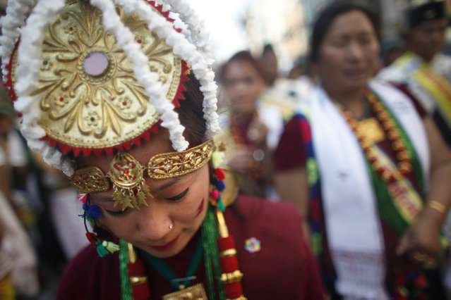 "A Nepalese Gurung community woman, wearing traditional attire, dances during a parade to mark their New Year know as ""Tamu Loshar"" in Katmandu, Nepal, Tuesday, December 30, 2014. The indigenous Gurungs, also known as Tamu, are celebrating their new year, welcoming the year of the Sheep. (Photo by Niranjan Shrestha/AP Photo)"