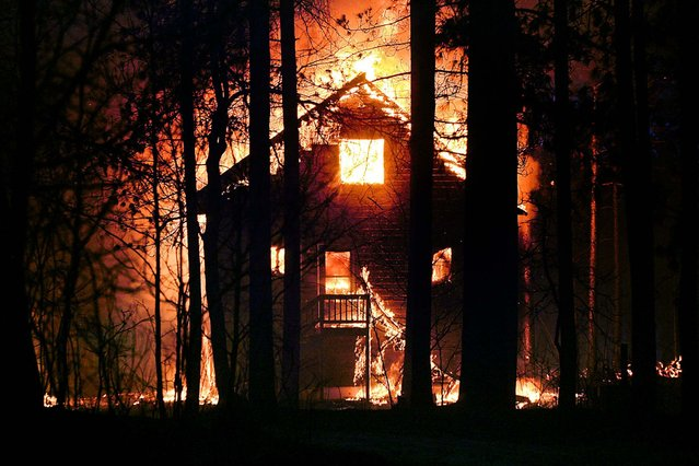 A home burns in Highland Township, Wisconsin, on May 14, 2013. Crews from Wisconsin and Minnesota tried to control a rapidly growing wildfire in northwestern Wisconsin that forced evacuations of the sparsely populated area.  Several structures were destroyed in a mostly rural and wooded area as the forest fire grew to 9 square miles, the Wisconsin Department of Natural Resources said. (Photo by Clint Austin/The Duluth News-Tribune)