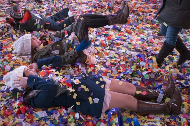 Revellers play in confetti along a street after midnight during New Year's Eve celebrations in Times Square, New York January 1, 2015. (Photo by Zoran Milich/Reuters)