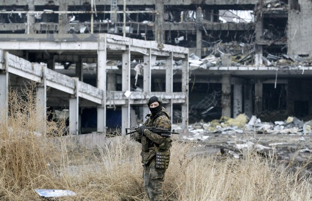 A member of the self-proclaimed Donetsk People's Republic forces stands near a building destroyed during battles with the Ukrainian armed forces, at the Donetsk airport, Ukraine November 20, 2015. (Photo by Alexander Ermochenko/Reuters)