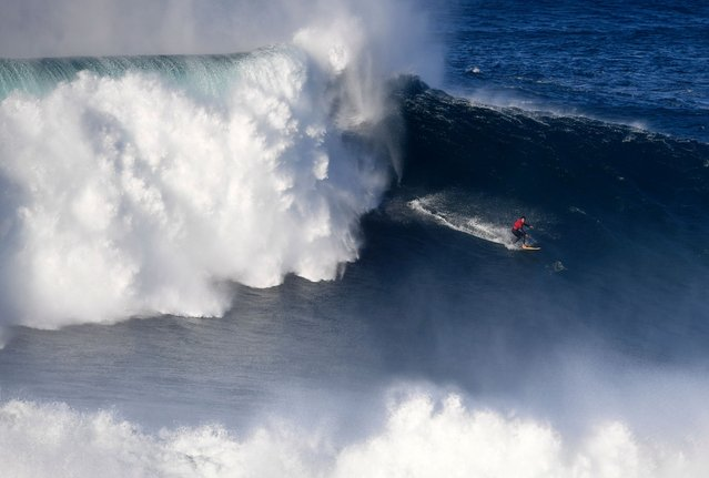 A surfer rides a wave off Praia do Norte (North Beach) near Nazare, central Portugal, on October 24, 2016. / AFP PHOTO / FRANCISCO LEONG