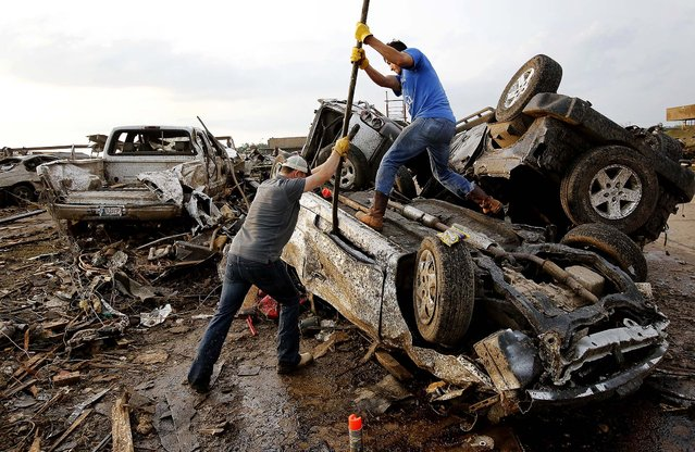 Two men attempt  to pry open a door on a car to check for victims in a business parking lot west of I-35 in Moore. (Photo by Jim Beckel/The Oklahoman)