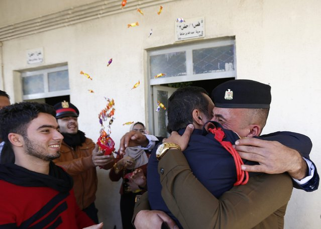 A officer is hugged as family members surround him at his graduation ceremony during Iraqi Army Day anniversary celebration in Baghdad January 6, 2015. (Photo by Thaier al-Sudani/Reuters)
