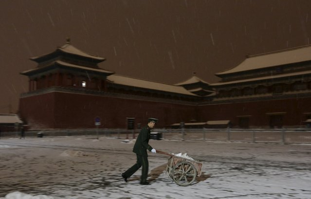 A paramilitary police officer pushes a wheelbarrow full of snow from the camp outside Wumen Gate of the Forbidden City during snowfall, at night in central Beijing, China, November 22, 2015. (Photo by Jason Lee/Reuters)
