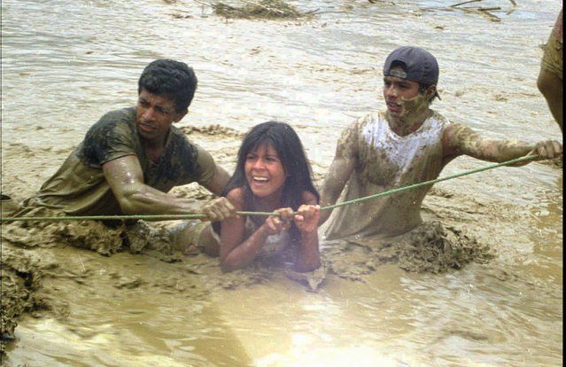 An unidentified woman is helped through floodwaters by Civil Defense volunteers after she left her home which was destroyed by rains attributed to El Nino, in Ecuador's Manabi province,  approximatly 124 miles (200 kms) north of Guayaquil, Wednesday May 6, 1998. According to Ecuadorean officials flooding and heavy rains attributed to the El Nino weather phenomenon have caused the over 200 deaths and left over 30,000 people homeless. (Photo by Mauro Andino/AP Photo).