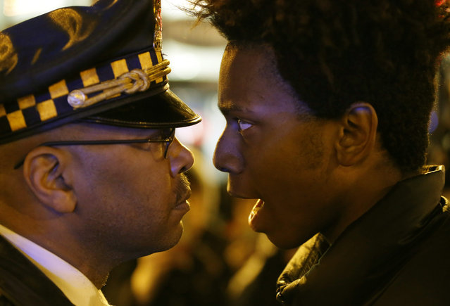 "Lamon Reccord, right, stares and yells at a Chicago police officer ""Shoot me 16 times"" as he and others march through Chicago's Loop Wednesday, November 25, 2015, one day after murder charges were brought against police officer Jason Van Dyke in the killing of 17-year-old Laquan McDonald. (Photo by Charles Rex Arbogast/AP Photo)"