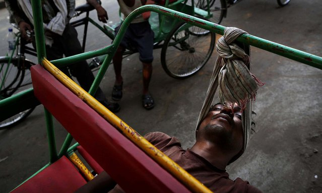 A bicycle rickshaw walla uses a scarf to rest his head while sleeping on his rickshaw in New Delhi, on June 6, 2013. Many of the men who make their living driving clients through the busy streets of the Indian capital sleep on their rickshaws, both to guard them and because they are from other parts of the country and have no permanent residence. (Photo by Kevin Frayer/Associated Press)