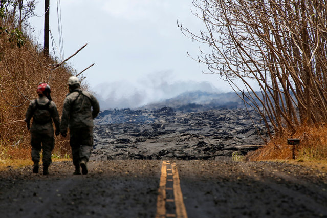 Soldiers from the Hawaii National Guard monitor sulfur dioxide gas levels near a lava flow in Leilani Estates during ongoing eruptions of the Kilauea Volcano in Hawaii, U.S., June 3, 2018. (Photo by Terray Sylvester/Reuters)