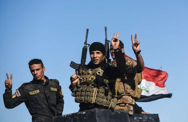 Iraqi forces flash the sign of victory as they drive their vehicle on November 3, 2016 near Gogjali, which lies on the eastern edge of Mosul, during their ongoing operation against jihadists of the Islamic State group to retake the city of Mosul. Some civilians were leaving Gogjali and others the eastern Mosul neighbourhood of Samah, in what may be a rare breach for civilians trapped inside the city. More than 21,000 people have fled to government-held areas since October 17, while thousands more may have been seized by IS for use as human shields, according to the United Nations. (Photo by Bulent Kilic/AFP Photo)