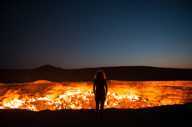 """Door to Hell"". Standing at the edge of the Darvaza Crater in Turkmenistan. Known as the Door to Hell, this flaming crater has been burning for decades, fueled by the rich natural gas reserves found below the surface. Location: Darvaza, Turkmenistan. (Photo and caption by Priscilla Locke/National Geographic Traveler Photo Contest)"