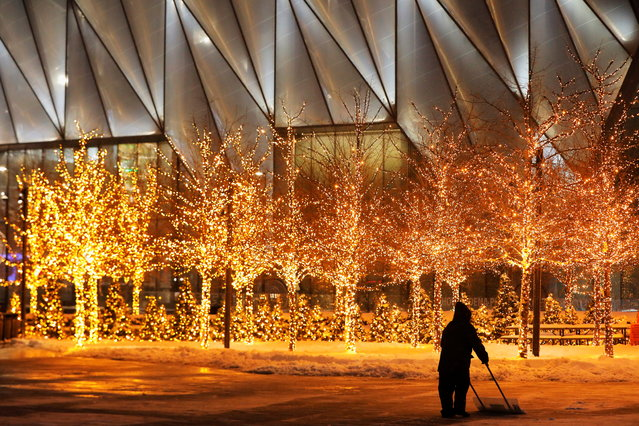 Worker clears ice and snow in front of illuminated trees in the Hudson Yards precinct of Manhattan, New York City on February 2, 2021. (Photo by Andrew Kelly/Reuters)