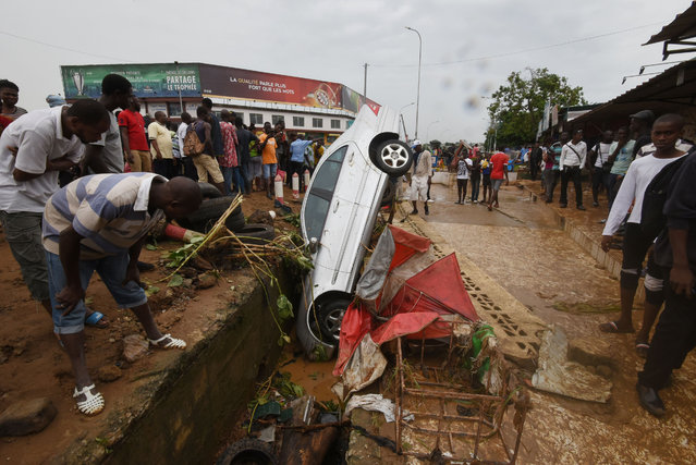 Pedestrians look at the wreckage of a vehicle lodged in a storm drain on a street in Abidjan on June 19, 2018, in which a man was reportedly found dead after floodwaters receded following an overnight downpour in the city. Fifteen people have died in Abidjan, Ivory Coast' s economic capital, during flooding caused by torrential rain overnight, Interior Minister Sidiki Diakite said. Rain poured down overnight on June 19, causing flash floods up to 2.5 metres (more than eight feet) deep, he said. (Photo by Sia Kambou/AFP Photo)