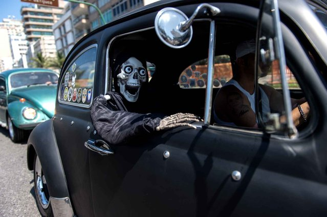 A man takes a skeleton doll in his Volkswagen Beetle, also known as Fusca, during a parade to celebrate the Brazilian national day of the Fusca, along Ipanema beach in Rio de Janeiro on January 20, 2015. (Photo by Yasuyoshi Chiba/AFP Photo)