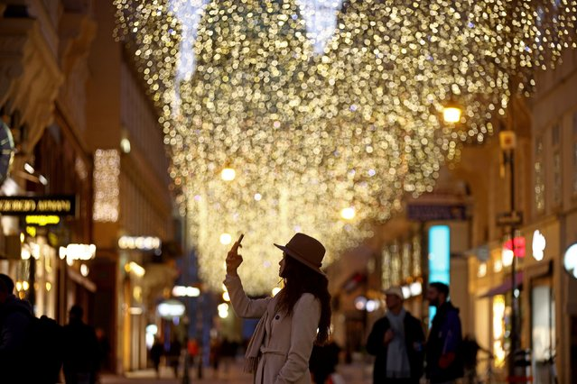 A woman takes a picture of Christmas lights at Kohlmarkt shopping street during second lockdown as the spread of the coronavirus disease (COVID-19) continues, in Vienna, Austria on November 17, 2020. (Photo by Lisi Niesner/Reuters)