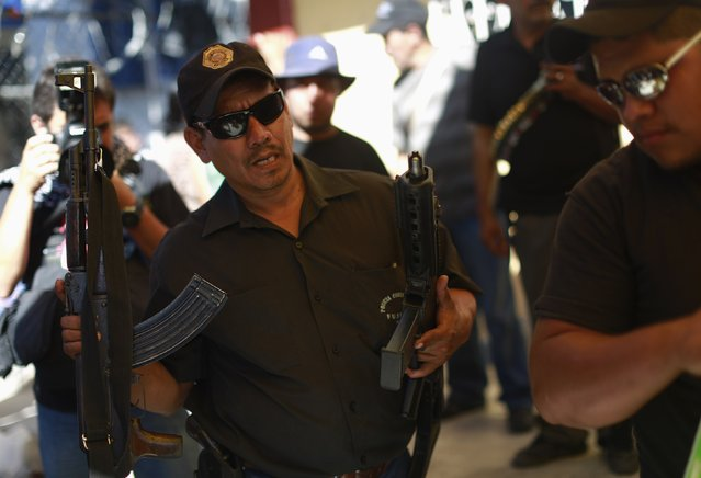 A member of the Community Police of the FUSDEG (United Front for the Security and Development of the State of Guerrero) carries weapons, that were seized from a house during an operation, to be displayed at a presentation in the village of Petaquillas, on the outskirts of Chilpancingo, in the Mexican state of Guerrero, February 1, 2015. (Photo by Jorge Dan Lopez/Reuters)