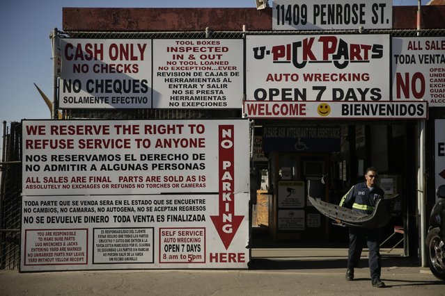 In this Wednesday, November 11, 2015 photo, a customer leaves Aadlen Brothers Auto Wrecking, also known as U Pick Parts, with a bumper he pulled from a junk car in the Sun Valley section of Los Angeles. (Photo by Jae C. Hong/AP Photo)