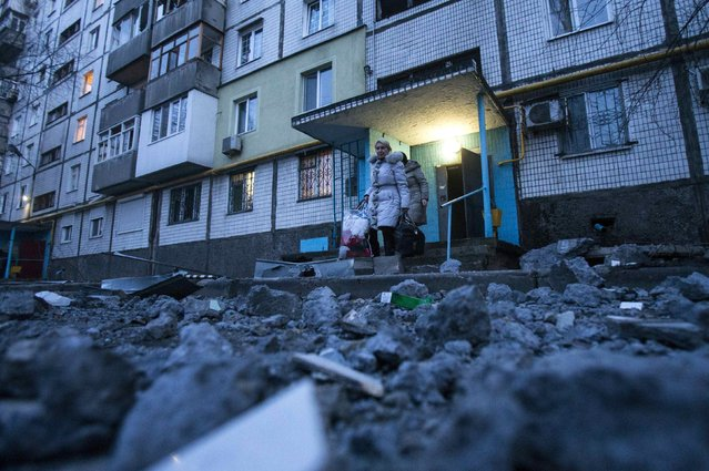 People walk out of a building near damaged pavement following a shelling, according to locals, in Donetsk February 4, 2015. (Photo by Maxim Shemetov/Reuters)