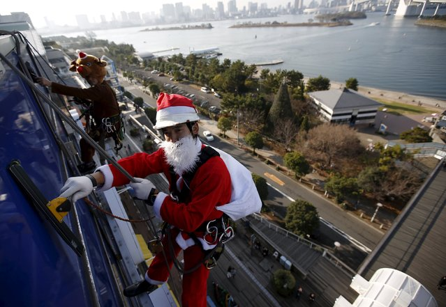 Window cleaners dressed as Santa Claus (R)  and a reindeer pose for photographers as he cleans a glass window at an event to celebrate the upcoming Christmas at a shopping mall in Tokyo December 24, 2015. (Photo by Issei Kato/Reuters)