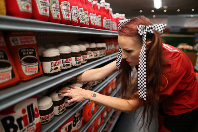 British artist Lucy Sparrow, 32, adjusts shelves in a art installation supermarket in which everything is made of felt, in Los Angeles, California on July 31, 2018. (Photo by Lucy Nicholson/Reuters)