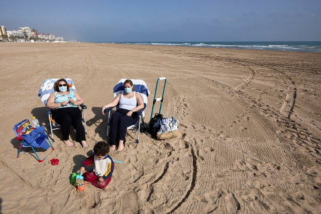People wear protective masks as they enjoy the sunny weather on the beach of Gandia in Valencia, Spain, 31 March 2021. Face mask is mandatory in all public spaces in the national territory, including beaches, parks or terraces, from 31 March. (Photo by Natxo Frances/EPA/EFE)