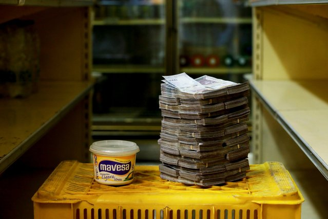 A container of 500gr of margarine is pictured next to 3,000,000 bolivars, its price and the equivalent of 0.46 USD, at a mini-market in Caracas, Venezuela August 16, 2018. It was the going price at an informal market in the low-income neighborhood of Catia. (Photo by Carlos Garcia Rawlins/Reuters)