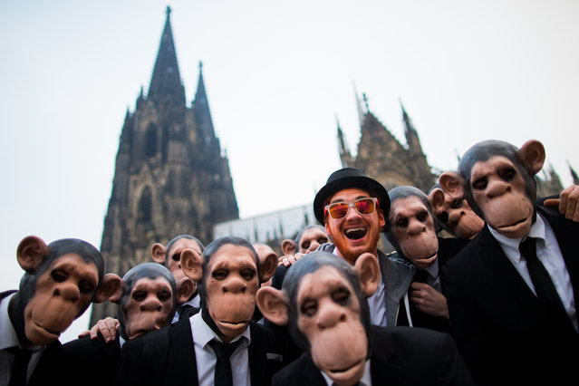 """Revelers wearing monkey masks celebrate carnival at the Alter Markt (Old Market square) in Cologne, Germany, February 12, 2015. Cologne celebrates the """"fifth season"""" from 11 to 17 February. (Photo by Rolf Vennenbernd/EPA)"""