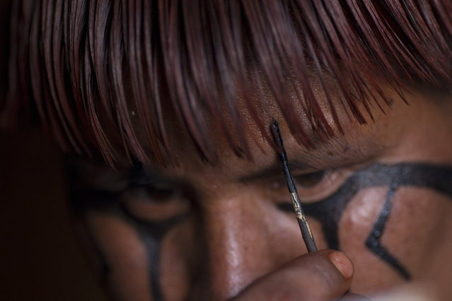 """A Waura Indian man paints his face to participate in this year's """"quarup"""", a ritual held over several days to honour in death a person of great importance to them, in the Xingu National Park, Mato Grosso State, August 24, 2013. This year the Waura tribe honoured their late cacique (chief), Atamai, who died in 2012, for his work creating the Xingu Park and his important contribution in facilitating communication between white Brazilians and Indians. (Photo by Ueslei Marcelino/Reuters)"""