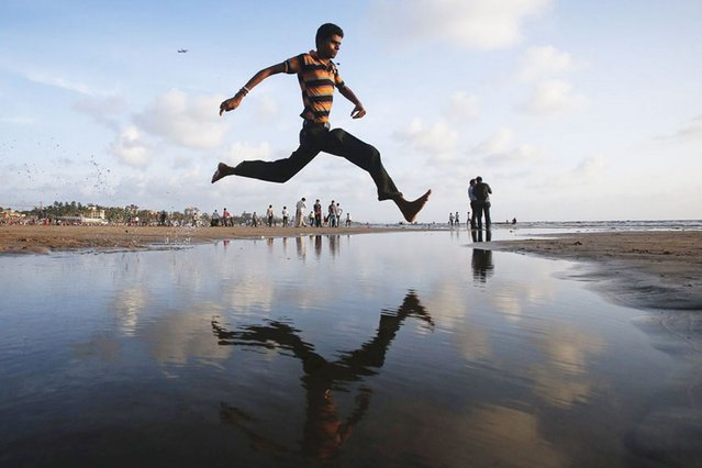 A man jumps over a water stream on a beach along the Arabian Sea in Mumbai, India, on September 3, 2013. (Photo by Danish Siddiqui/Reuters)