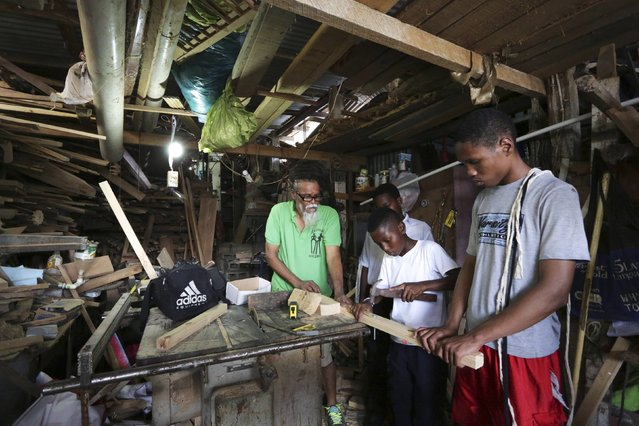 Kaisokah Moko Jumbies cultural group founder Junior Bisnath (L) teaches young members of his group how to make the stilts they will use in their performing routines in the workshop of his San Fernando home, which is used as a base for the group, February 9, 2015. (Photo by Andrea De Silva/Reuters)