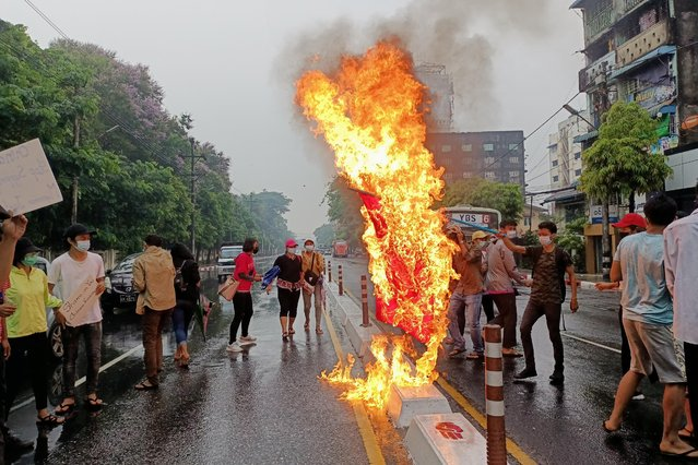 Anti-coup protesters burn a Chinese national flag during a demonstration against Beijing's support for the Myanmar military in Yangon, Myanmar on April 5, 2021. (Photo by Reuters/Stringer)