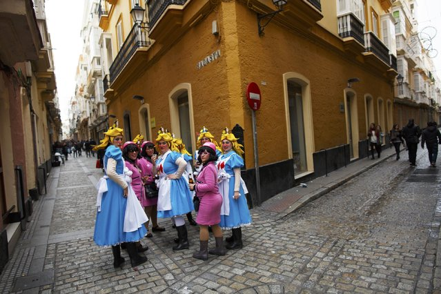 Women in fancy costumes look on during the Carnival of Cadiz, southern Spain February 15, 2015. The carnival will run until February 22. (Photo by Marcelo del Pozo/Reuters)