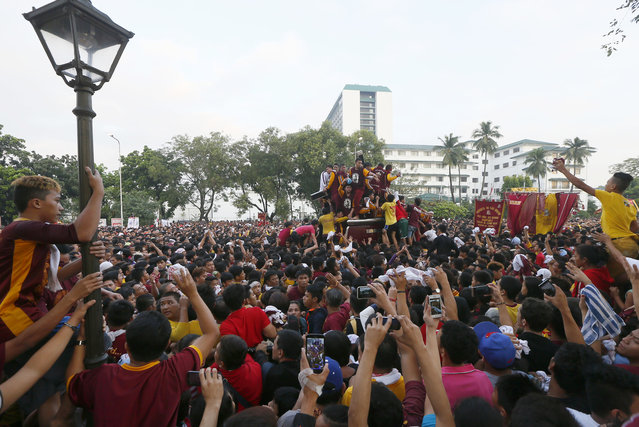 Catholic devotees take photos and wave towels as the image of the Black Nazarene passes by in a raucous procession to celebrate its feast day in Manila, Philippines, Saturday, January 9, 2016. (Photo by Bullit Marquez/AP Photo)