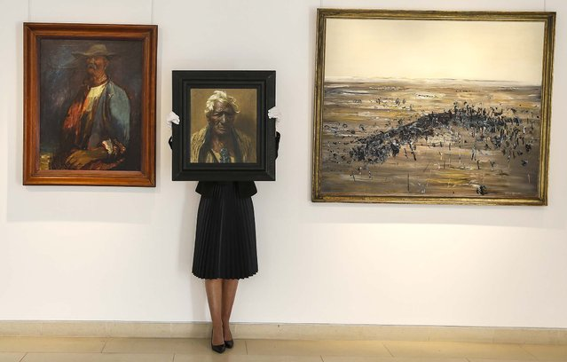 """A Christie's employee holds the painting, """"An Aristocrat, Atama Paparangi"""" by Charles Frederick Goldie, at left is """"Old Larsen"""" by Sir George Russell Drysdale, and at right is """"Lysterfield"""" by Frederick Ronald Williams, during a media tour at the auction rooms in London, on September 20, 2013. The painting is estimated at to bring between $321,000 and $481,000 Ul be during the Australian Art sale. (Photo by Kirsty Wigglesworth/Associated Press)"""