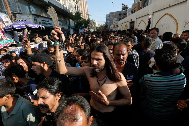 A Pakistani Shi'ite Muslim man holds knives before a flagellation with others during Chelum, a procession to mark the fortieth day after the death of Imam Hussain, grandson of the Prophet Muhammad, in Karachi, Pakistan, November 21, 2016. (Photo by Akhtar Soomro/Reuters)