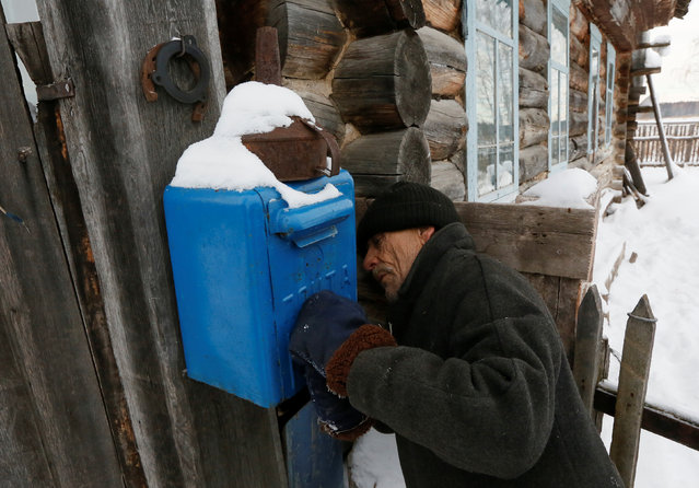 Mikhail Baburin, 66, inspects a post box on a fence of his house in the remote Siberian village of Mikhailovka, Krasnoyarsk region, Russia, December 5, 2016. Baburin, a former Navy man, barge worker and employee of a military plant in Krasnoyarsk, is the last inhabitant of Mikhailovka, which was founded in the 19th century by migrants from Russia's Mordovia region. He moved in 2000 to Mikhailovka where he was born and has lived there all alone for the last 10 years with only domestic animals. (Photo by Ilya Naymushin/Reuters)