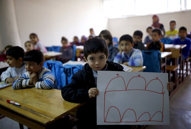 Syrian refugee boy Ali Ristmo, 7, shows his drawing depicting a mosque during a lesson with his classmates in Yayladagi refugee camp in Hatay province near the Turkish-Syrian border, Turkey, December 16, 2015. (Photo by Umit Bektas/Reuters)