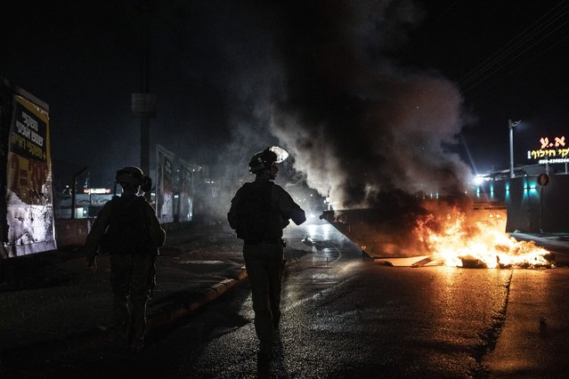 Israeli police patrol during clashes between Arabs, police and Jews, in the mixed town of Lod, central Israel, Wednesday, May 12, 2021. As rockets from Gaza streaked overhead, Arabs and Jews fought each other on the streets below. Rioters torched vehicles, a restaurant and a synagogue in one of the worst spasms of communal violence that Israel has seen in years. (Photo by Heidi Levine/AP Photo)
