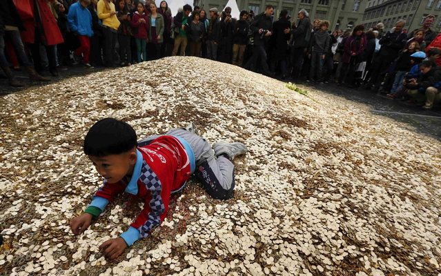 """A child plays on a pile of 8,000,00 five cent coins in the centre of the Federal Square during an event organised by the Committee for the initiative """"CHF 2,500 monthly for everyone"""" (Grundeinkommen) in Bern October 4, 2013. The Committee delivered 126,000 signatures to the Chancellery on Friday to propose a change in the constitution to implement their initiative. The initiative aims to have a minimum monthly disposal household income of CHF 2,500 (US$ 2,700) given by the government to every citizen living in Switzerland. (Photo by Denis Balibouse/Reuters)"""
