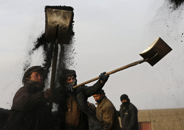 Labourers shovel coal onto a truck at a coal dump site outside Kabul January 19, 2015. Each labourer earns an average of $10 per working day, with most of them coming come from the northern provinces, leaving their families behind to find work in the capital. (Photo by Mohammad Ismail/Reuters)